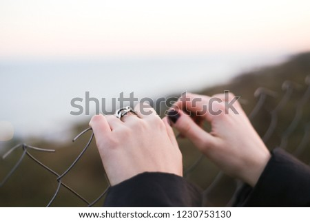 woman's hand on a metal fence. #1230753130