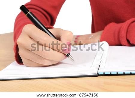 woman's hand writing on a spiral book on the table - stock photo
