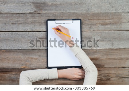 woman\'s hand writing on paper over wooden table