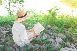 woman sitting on stone and reading a book in summer