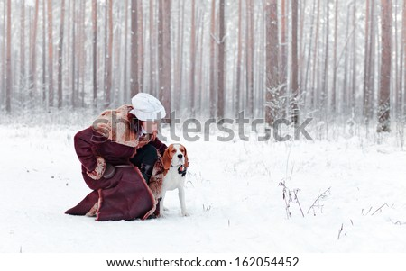 woman walk with dog in snowy forest