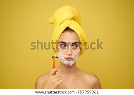woman with a razor, a towel on her head, facial skin care