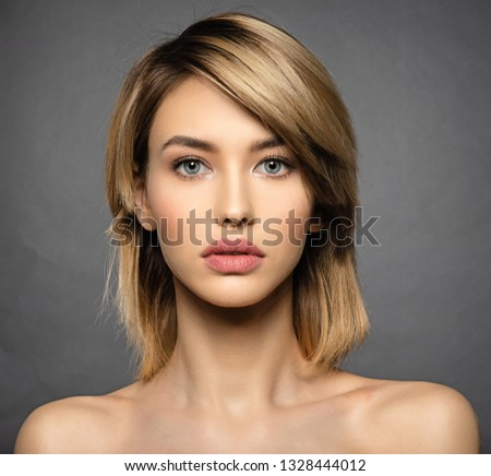 Woman with beauty face and clean skin.  Sexy blonde woman.  Attractive blond model with blue eyes. Fashion model with a smokey makeup. Closeup portrait of a pretty woman. Creative short hairstyle.