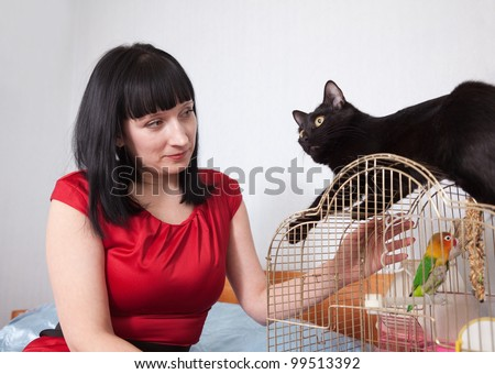 woman with  black cat and parrot in home