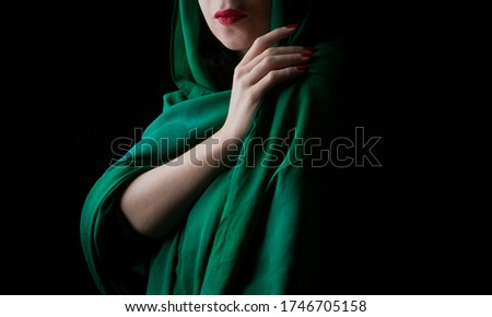 Woman with green veil and red lipstick in black background Stockfoto ©