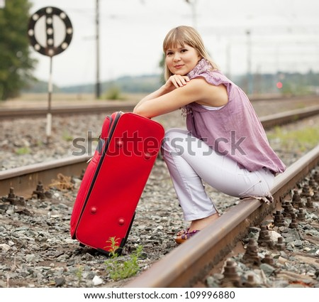 woman with luggage sitting on rail