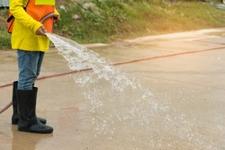 Woman with safety cloth and long boot  cleaning driveway with water at construction site area.Professional worker splashing water.