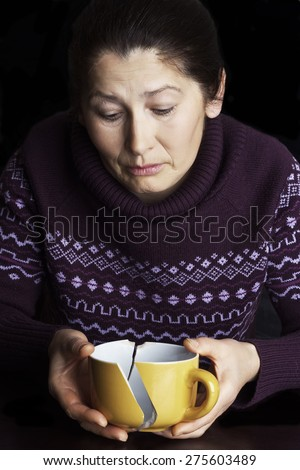 Woman with the broken cup in hand on a black background.