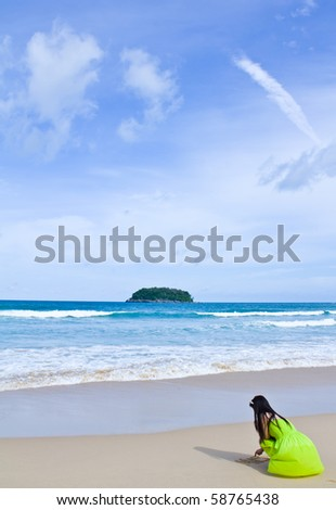 woman writing on sand  at the beach
