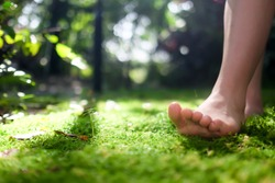 women bare feet walking on moss with sunlight
