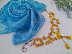 Wonderful natural yellow  amber necklace with decorative blue silk flower  lie on a white silky background.