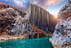 Wonderful Nature landscape. Incredible view on river in canyon with black basalt columns  under sunlight, Tipical Icelandic scenery. Studlagil Canyon during sunset. Iconic location for photographers.
