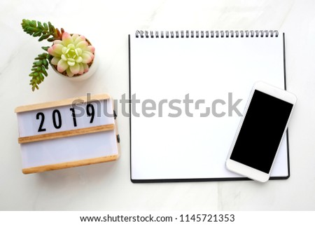 2019 wood box, blank notebook paper, smart phone with blank screen on white marble background, 2019 new year mock up, template, flat lay