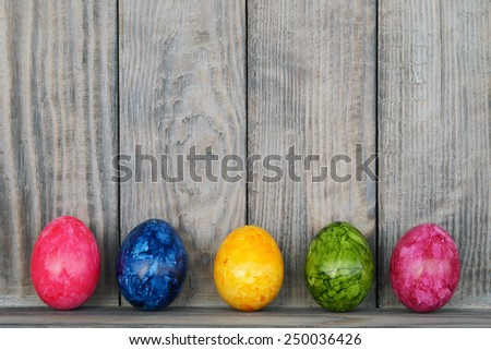wooden background with painted eggs                               - Shutterstock ID 250036426