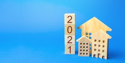 2021 wooden blocks and miniature house. Real estate concept. Family budget planning. Investments, plans, savings. Mortgage and mortgage rates. Forecasts. Loan. Refinance home