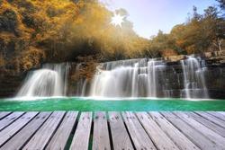 Wooden bridge over beautiful autumn waterfall at Loei province, Thailand.