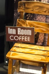 Wooden chair with a sign offering hotel rooms and coffee. Bad and breakfast. Vintage style