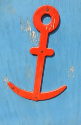 wooden red anchor on a blue wooden surface with peeling paint
