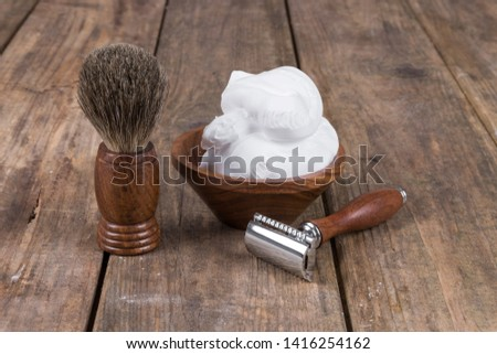 Wooden shaving razor and shaving brush with shaving foam on a rustic wooden table