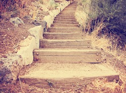 wooden steps going up a hill toned with a retro vintage instagram filter effect app or action