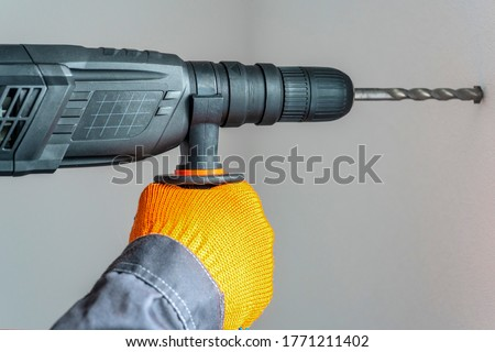 workman hand with a rotary hammer. Hands in protective gloves with hammer drill perforator. close-up Stockfoto ©