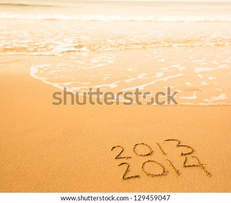 2013 - 2014 written in sand on beach texture - soft wave of the sea.