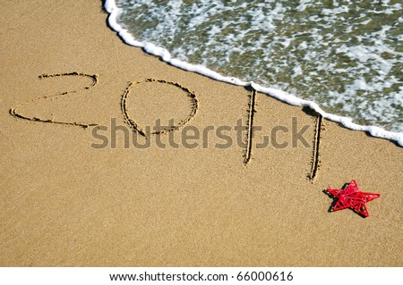2011 written in the sand of a beach with a Christmas star