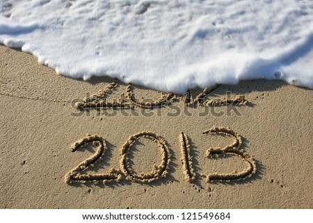 2013 written in the sand with 2012 washed away by the surf. - stock photo
