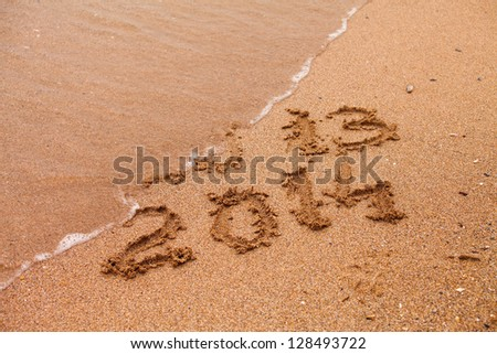 2014 written in the sand with 2013 washed away by the wave