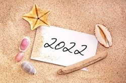 2022, written on a note in the sand with seashells, ravel new year card