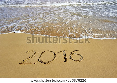 2016 written on sand beach near sea - happy new year concept #353878226
