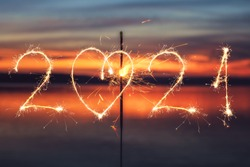 2021 written with Sparkle firework on sunset background, happy new year 2021 concept.