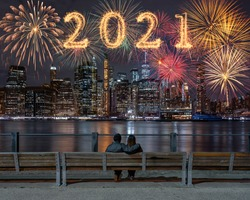 2021 written with Sparkle firework with multicolor of fireworks on back side couple sitting and looking New york Cityscape background, USA downtown skyline,Happy new year and merry Christmas concept