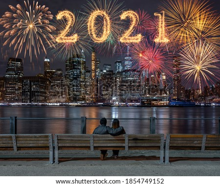 Photo of  2021 written with Sparkle firework with multicolor of fireworks on back side couple sitting and looking New york Cityscape background, USA downtown skyline,Happy new year and merry Christmas concept
