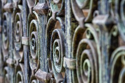 Wrought iron fence. Detail of an old retro iron fence made with decorated ironwork elements. Old and worn, still showing some of its former splendor