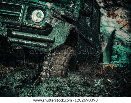 4x4 travel trekking. Offroad vehicle coming out of a mud hole hazard. Bottom view to big offroad car wheel on country road and mountains backdrop #1202690398