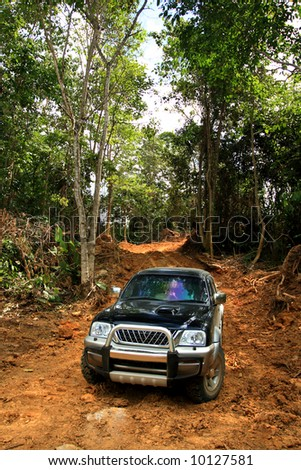 4x4 vehicle driving offroads in a difficult dirt terrain - stock photo