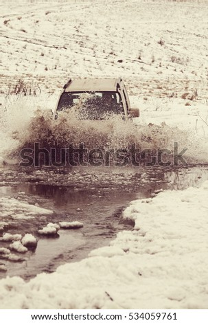 4x4 vehicles drive through the water splashing in winter season #534059761