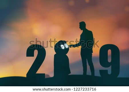 2019 year artificial intelligence or ai futuristic concept, Silhouette  Business man stand and point hand to command or control assistant robot, industry 4.0 trend of automation robot in 2019 future