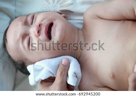1 year Asian baby boy get sick,he has high fever, Father making tepid sponge for him.A tepid sponge bath may reduce body temperature .Baby is crying. Stockfoto ©