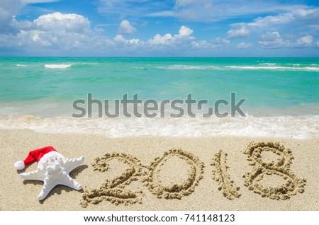 2018 year beach background near ocean with starfish in Santa Hat  #741148123