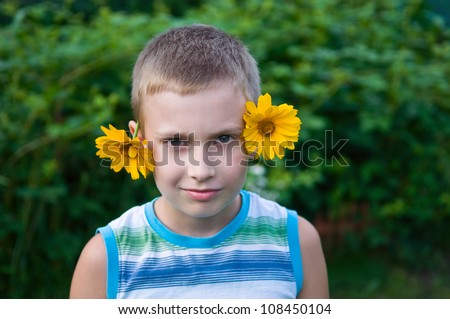8-year boy with flowers on ears having fun