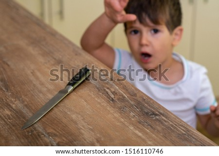 3 year child standing and trying to get a kitchen knife. Safety for home health-care, common dangers for and risk kids at home. Selective focus