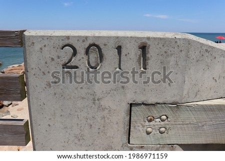 2011 year craved into concrete ocean beach and sand background Foto stock ©