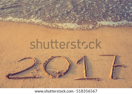 2017 year of the awakening - Numbers of the date 2017 drawn on the sand of a beach at sunrise with a soft wave touching the shore. In the Chinese calendar it would be the year of the fire rooster.  #518356567