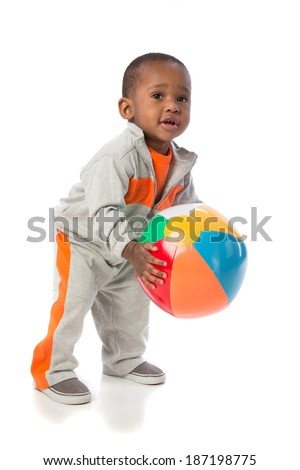 Year old african american baby boy standing holding beach ball on