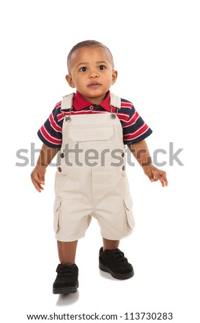 1-year old african american boy standing with curious expression looking at camera