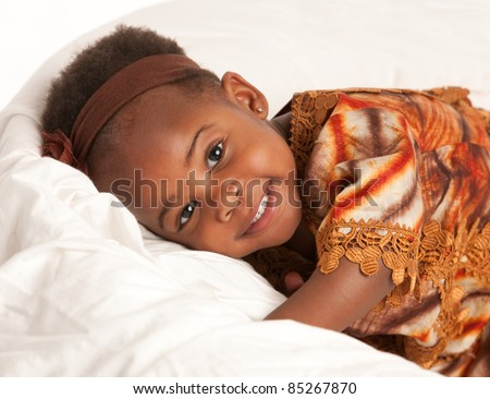 3 year old African American girl in colorful costume sit on bed