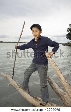 11 year old Asian boy balancing on log in water near Kairaki / mouth of Waimakariri River MR - stock photo