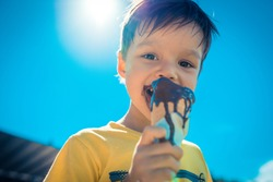 3 year old asian caucasian boy enjoying a melting chocolate ice-cream on a sweltering hot summer day. Clear blue summer sky in background